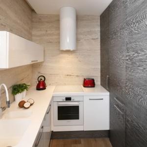 Podobny dąb gości również na ścianie kuchni oraz cokołach zabudowy kuchennej. W zestawieniu z jasnym drewnem na ścianie nad blatem stanowi piękny, wysmakowany i bardzo przytulny duet. Projekt: Agnieszka Ludwinowska. Fot. Bartosz Jarosz