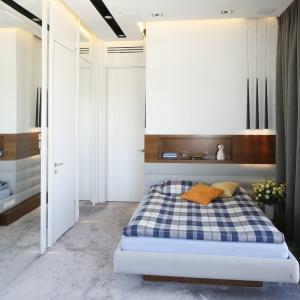 Tapicerowany zagłówek w kolorze łóżka jest jednocześnie okładziną ścienną, powyżej dekoracyjna wnęka wykończona fornirem. Projekt: Monika i Adam Bronikowscy. Fot. Bartosz Jarosz