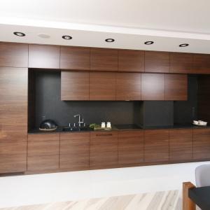 Głęboki brązowy odcień nowoczesnych mebli kuchennych dodaje otwartej przestrzeni dziennej elegancji. Proj. wnętrza Jan Sikora.