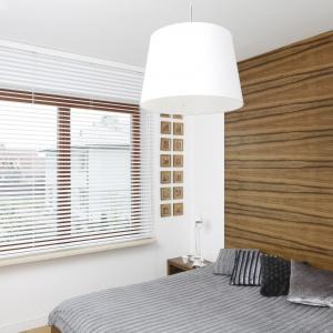 Ściana z rysunkiem drewna wprowadza do sypialni przytulną atmosferę. Proj. wnętrza Agnieszka Ludwinowska.
