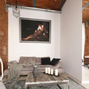 """Salon stanowi przytulny kącik, wktórym można się zrelaksować. Znajduje się tutaj wygodna kanapa, stolik kawowy itelewizor. Na ścianie za kanapą wisi kopia obrazu """"Ekstaza św. Franciszka"""" namalowanego przez Caravaggia. Projekt: Tomasz Jasiński. Fot. Bartosz Jarosz"""