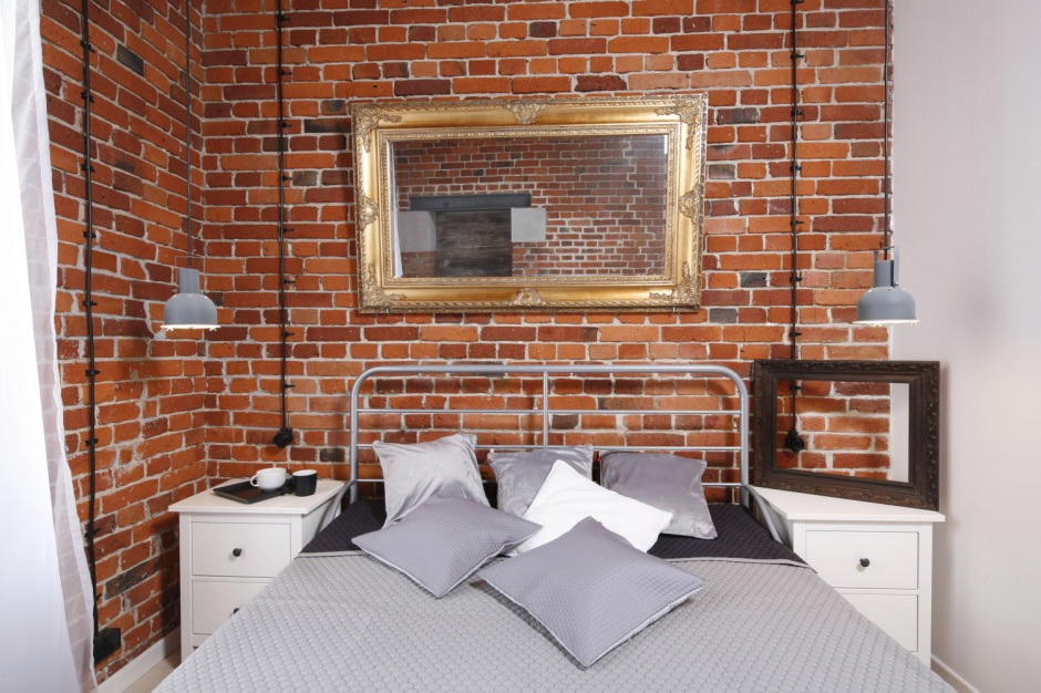 Wsypialni znalazło się proste stalowe łóżko,drewniane szafki oraz wielkie stare lustro.  Projekt: Tomasz Jasiński. Fot. Bartosz Jarosz