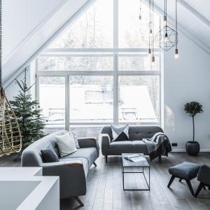 W tym salonie urządzonym w skandynawskim stylu drewniana podłoga przełamuje śnieżną biel i ociepla wizualnie wnętrze. Fot. Nobifloor/Dekorian, kolekcja Modern