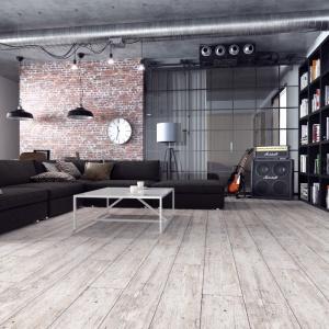W aranżacji salonu w stylu loft drewno jest wspaniałym kontrastem dla cegły i betonu, a w surowej wersji staje się elementem jednocześnie ocieplającym, jak i dopełniającym szorstki wystrój. Fot. Classen, panele Galaxy 4V Świerk Viviero.