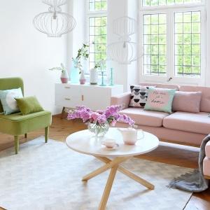 Białe ściane, białe skrzyniowe meble, drewniana przytulna podłoga oraz wypoczynkowe meble w pięknych kolorach wiosny. Pudrowy róż w połączeniu z zielenią sprawiają, że ten jasny salon nabiera życia. Fot. Westwing