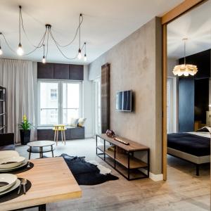 """""""Ceglana"""" ściana usytuowana jest na przeciw ściany wykończonej tynkiem z efektem betonu. Za przegrodą w postaci drewnianej balki znajduje się sypialnia. Fot. Nowa Papiernia/Anna Kopec"""