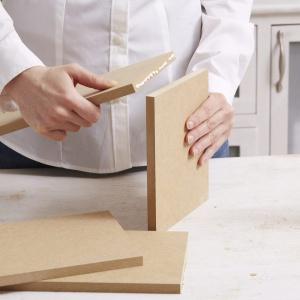 Krok 3: Teraz sklej pozostałe cztery elementy z płyty MDF klejem do drewna, aby utworzyły budkę i pozostaw ją do wyschnięcia.  Następnie użyj kleju do drewna aby po obydwu stronach budki zamocować ścianki w kształcie ptaka. Upewnij się, że budka jest przyklejona na równi z tylną krawędzią elementów bocznych. Fot. Dremel.