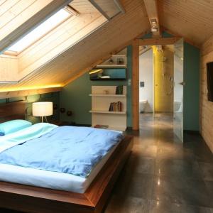 Ściany w tej sypialni wykonano z prawdziwym drewnianych bali. Z jasną barwą drewna skontrastowano ciemną kolorystykę drewnianego łóżka. Projekt: Tomasz Motylewski, Marek Bernatowicz. Fot. Bartosz Jarosz