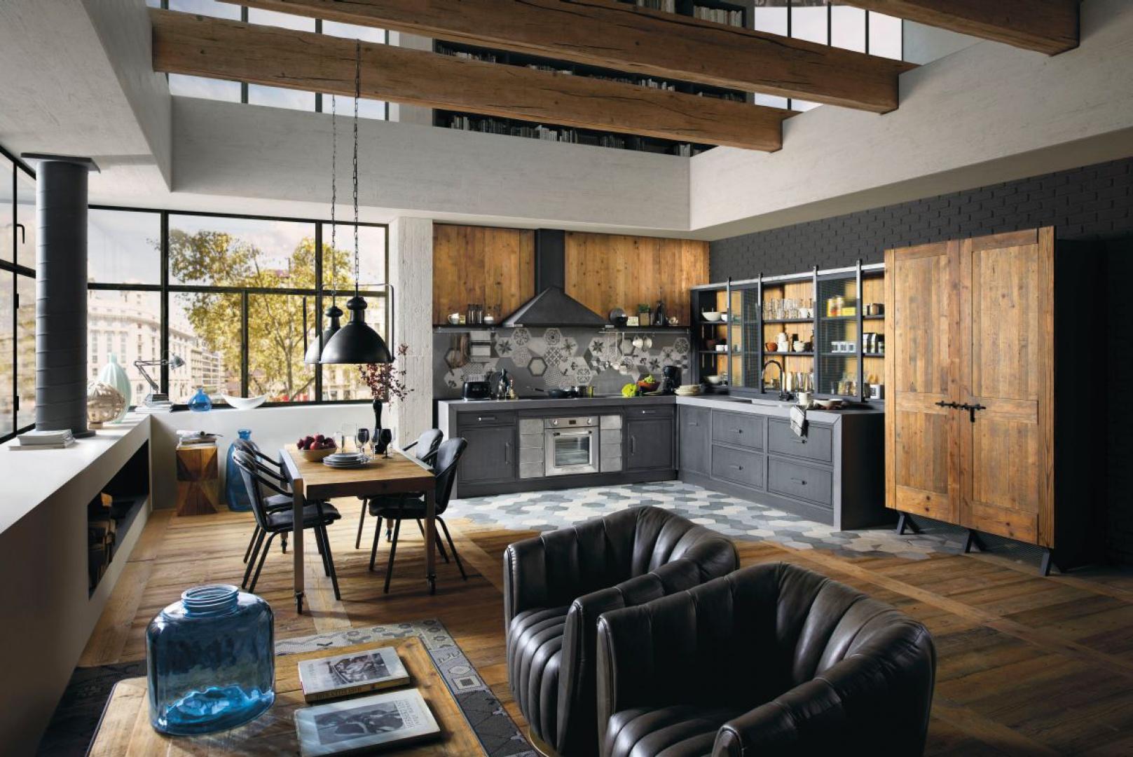 Inspiracja od marki Marchi Cucine: odsłonięte belki stropowe górują nad przestrzenią kuchni z jadalnią. Na metalowym łańcuchu zwisa z nich loftowa lampa. Meble kuchenne są utrzymane w kolorach szarości, a wysoka zabudowa została tak wystylizowana, że wygląda na zrobioną ze starych desek. Fot. Marchi Cucine, kuchnia Brera 76