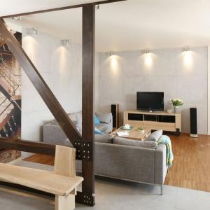 Mieszkanie urządzono w stylu industrialnym, a przedpokój od salonu oddzielają ciekawie zaaranżowane drewniane belki. Ścianę częściowo należącą do przedpokoju, cześciowo zdobiącą salon pokrywa industrialna fototapeta. Projekt: Marta Kruk. Fot. Bartosz Jarosz