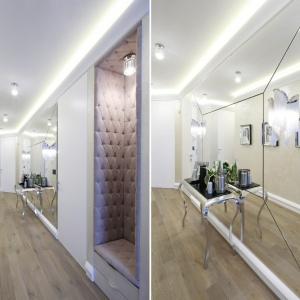 W dość wąskim przedpokoju przestrzeń znacznie powiększa ogromne lustro, złożone z mniejszych części o geometrycznej formie. Zamiast na tradycyjnym stołku, usciąść możemy w przytulnej niszy, wyłożonej pikowaną tkaniną. Projekt: Karolina Łuczyńska. Fot. Bartosz Jarosz