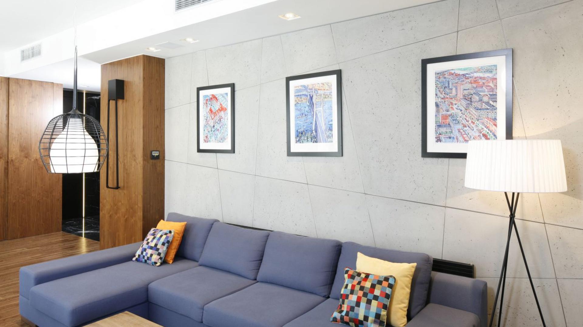 Scianę w salonie pokryto tynkiem z efektem betonu, w którym odciśnięto asymetryczne linie, tworzące geometryczny rysunek na ścianie. Projekt: Monika i Adam Bronikowscy. Fot. Bartosz Jarosz