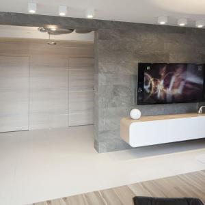 W tym domu salon urządzono w stylistyce lat 60. z opływowymi, futurystycznymi kształtami. Podobny charakter ma podwieszana szafka RTV. Projekt: Marta Kilan. Fot. Bartosz Jarosz