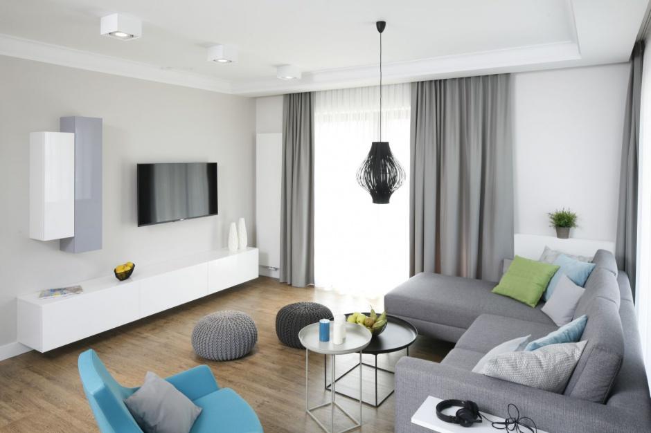 Długa, poprowadzona niemal przez szerokość całej ściany szafka RTV wykończona została w połyskującej bieli. Wpisuje się idealnie w nowoczesny styl salonu. Projekt: Małgorzata Galewska. Fot. Bartosz Jarosz