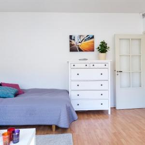 Obok narożnika ustawiono łóżko, przy którym stoi biała komoda. Fot. Svenksfast.se