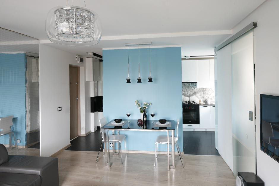 To małe mieszkanie ma zaledwie 36 metrów kwadratowych powierzchni. Jadalnię urządzono przy ściance działowej pomiędzy kuchnią i salonem. Aby mocniej zaznaczyć obecność strefy jadalni, ściankę pomalowano błękitną farbą. Projekt: Marta Kilan. Fot. Bartosz Jarosz