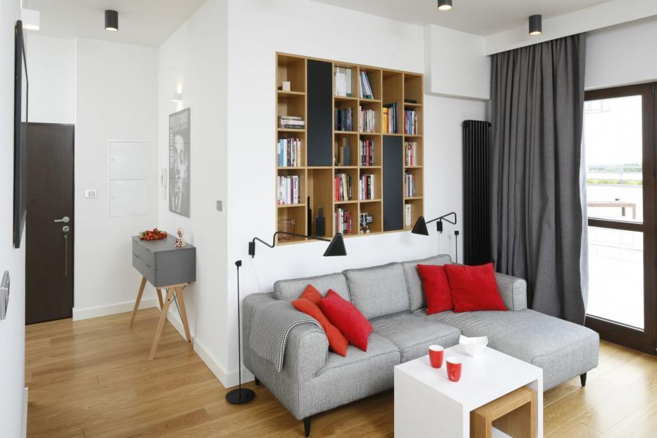 Nad kanapą w salonie zaplanowano wnękę w ścianie, w której umieszczono nowoczesną biblioteczkę. Asymetrycznie rozmieszczone półki, poprzecinane pasami matowych antracytowych frontów prezentują się bardzo efektownie. Projekt: Małgorzata Łyszczarz. Fot. Bartosz Jarosz