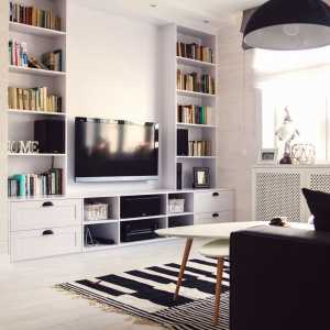 Propozycja dla miłośników zarówno dobrej lektury, jak i dobrego filmu. Po obu stronach strefy TV zamontowano poprowadzone pod sam sufit półki, które funkcjonują jako biblioteczka. Projekt: Meblościanka Studio. Fot. Maua Fotografia