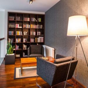 W jednorodzinnym domu na salonik z biblioteczką przeznaczono powierzchnię na antresoli otwartej na salon. Książki znalazły miejsce na wysokim, ciągnącym się od podłogi po sufit regale. Projekt: Pracownia Projektowa Wnętrz Viva Design. Fot. Tadeusz Późniak