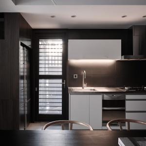 Kuchnię urządzono w centrym domu. Ściany utrzymano w kolorystyce harmonizującej z resztą wnętrza. Tym co zaznacza obecność aneksu kuchennego są białe meble. Projekt: Z-AXIS Design. Fot. Hey!Cheese Photography