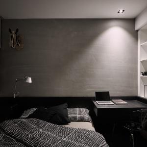 W kolejnej sypialni postawiono na monochromatyczną kolorystykę: czerń, biel i szarość w postaci betonowego tynku. Projekt: Z-AXIS Design. Fot. Hey!Cheese Photography