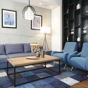 Na podłodze w salonie położono dywan utrzymany w tych samych barwach, co meble wypoczynkowe, geometrycznym wzorem nawiązujący do ściany za kanapą. Projekt: Monika i Adam Bronikowscy. Fot. Bartosz Jarosz