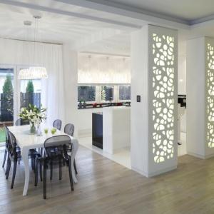 Kuchnię od strony salonu i holu zamykają oryginalne kolumny, wykończone ażurowymi panelami, podświetlonymi od środka. Takie rozwiązanie organizuje przestrzeń, ale również stanowi niezwykle efektowny element dekoracyjny. Projekt: Katarzyna Mikulska-Sękalska. Fot. Bartosz Jarosz