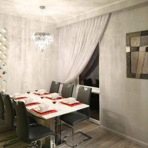 Ścianka działowa pomiędzy kuchnią i salonem z jadalnią jest tylko częściowa, a przy tym udekorowana ażurową perforacją, przepuszczającą światło. Projekt: Małgorzata Goś. Fot. Bartosz Jarosz
