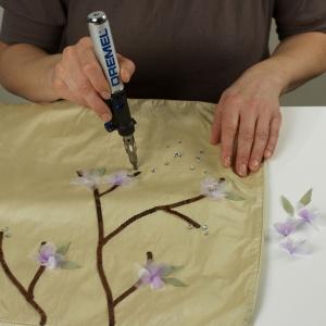 Krok 4  Z zielonej tkaniny wytnij liski i użyj pistoletu do klejenia Dremel Glue Gun do przyklejenia ich na poduszkach (liście możesz także wykonać  z jasnozielonych cekinów). Dodaj kilka ozdobnych kamyczków, które zamocujesz na poduszce na gorąco lutownicą. Mogą one symbolizować pączki kwiatów na gałązkach. Możesz także uformować z nich kwiaty. Fot. Dremel