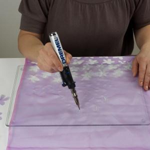 Krok 1  Z organzy wytnij wzory kwiatków, używając do tego lutownicy Dremel Versatip z końcówką do lutowania. Do grubszych tkanin zamiast końcówki do lutowania użyj noża do cięcia Versatip. Krok 2 Aby wykonać cały kwiatek, złóż ze sobą trzy wycięte z organzy kształty, ściśnij je i połącz ze sobą, dotykając końcówką lutownicy pośrodku z tyłu kwiatka. Fot. Dremel