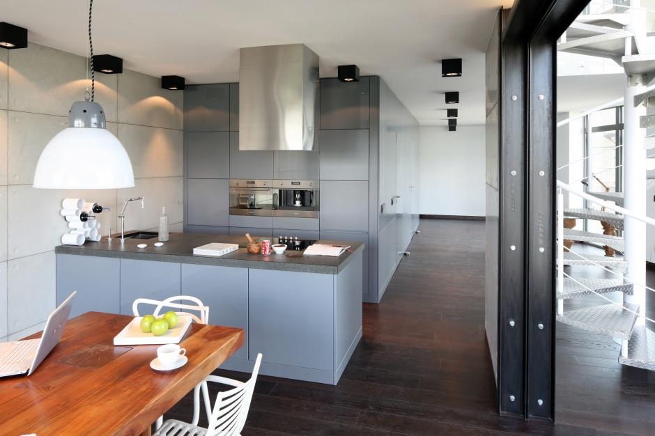 Elegancka kuchnia w stylu loft. Szara zabudowa kuchenna w macie harmonizuje kolorme i formą z betonową ścianą. Projekt: Justyna Smolec. Fot. Bartosz Jarosz