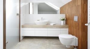Rolę główną w tej eleganckiej łazience gra wygodna wanna oraz jej gustowna oprawa z naturalnych materiałów.Stonowane kolory sprawiają, że aranżacja ma ponadczasowy charakter.