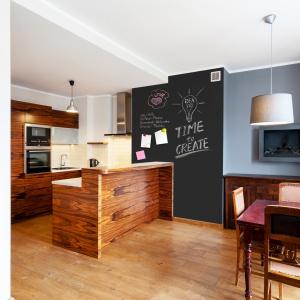 Ścianę na granicy kuchni z jadalnią pomalowano farbą tablicową. Fot. Primacol Decorative