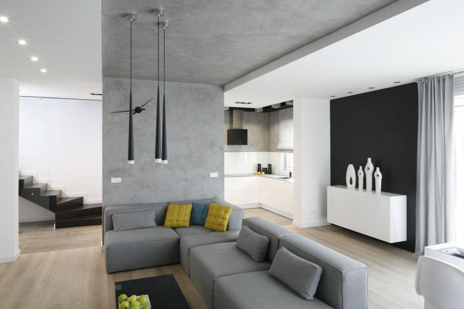 Przestrzeń zaznaczającą kącik wypoczynkowy zaakcentowano ścianką działową, przechodzącą w podwieszany sufit. Powierzchnie w poziomie i pionie pokryto tynkiem betonowym. Projekt: Karolina Stanek-Szadujko i Łukasz Szadujko. Fot. Bartosz Jarosz
