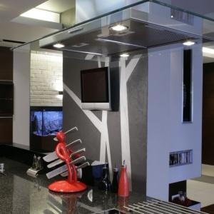 Na ścianie oddzielającej kuchnię od reszty mieszkania zamontowano niewielki telewizor, który można oglądać pracując przy wyspie kuchennej. Projekt: Liliana Masewicz-Kowalska. Fot. Bartosz Jarosz