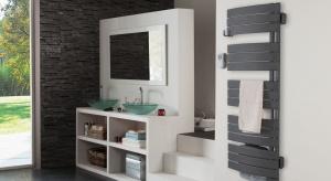 Sterowany radiowo grzejnik, w kolorze antracytowym, wpasuje się zarówno do ciepłej łazienki, w której przeważa drewno, jak i do industrialnej, z surową posadzką i kamieniem na ścianie.
