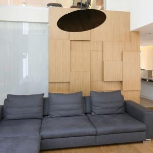 Asymetryczna, trójwymiarowa drewniana bryła funkcjonuje jako ściana za kanapą w tym nowoczesnym, otwartym na dwie kondygnacje salonie. Projekt: Katarzyna Kiełek, Agnieszka Komorowska-Różycka. Fot. Bartosz Jarosz