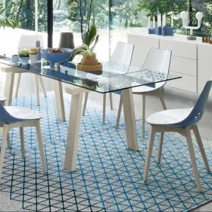 Szklany blat o błękitnym kolorze wsparto na ciekawie rozwierających się drewnianych podstawach. Stołowi towarzyszą nowoczesne krzesła. Fot. Kler, stół Levante