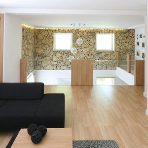 Z antresoli nad salonem można podziwiać wysoką na dwie kondygnacje ścianę z kamienia, na którego pokładach wzniesiono dom. Projekt: Małgorzata Błaszczak. Fot. Bartosz Jarosz
