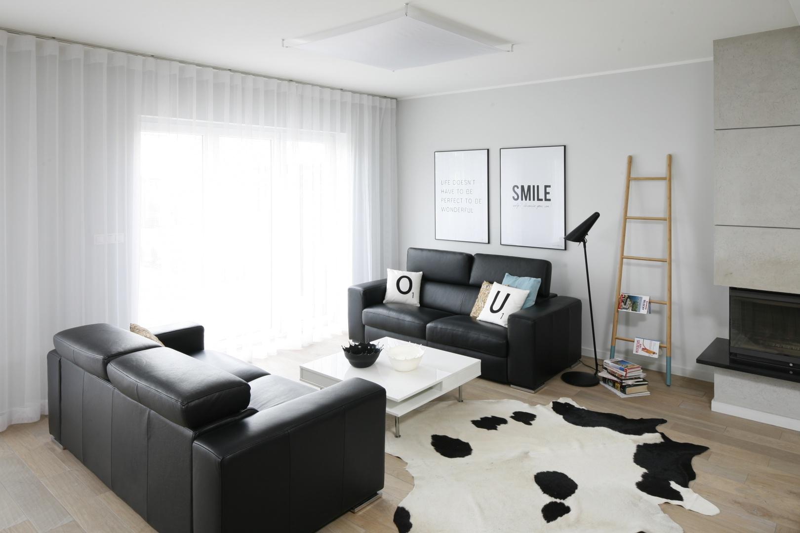 Urządzony w skandynawskiej manierze salon zdominował duet czerni i bieli w równych proporcjach, dla których tło stanowią szare ściany. Projekt: Beata Kruszyńska. Fot. Bartosz Jarosz