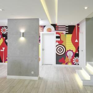 Tynk dekoracyjny z efektem betonowych płyt świetnie wygląda w otwartej przestrzeni strefy dziennej, świetni kontrastuje z kolorową tapetą. Projekt: Dominik Respondek. Fot. Bartosz Jarosz