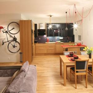 W przestrzeni pomiędzy kuchnią i salonem urządzono niewielką jadalnię. Pomiędzy stołem a zabudową kuchenną wpasowano mały półwysep. Projekt: Izabela Szewc. Fot. Bartosz Jarosz