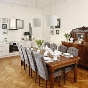 Solidny duży drewniany stół na pięknych stylizowanych nogach stanowi centrum spożywania posiłków. Projekt: Iwona Kurkowska. Fot. Bartosz Jarosz