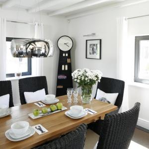 Posiłek goście zdjedzą przy pięknym, klasycznym, drewnianym stole w otorzeniu eleganckich drobiazgów - pięknego zegara, delikatnych firan w oknach i deisgnerskiego oświetlenia. Projekt: Kamila Paszkiewicz. Fot. Bartosz Jarosz