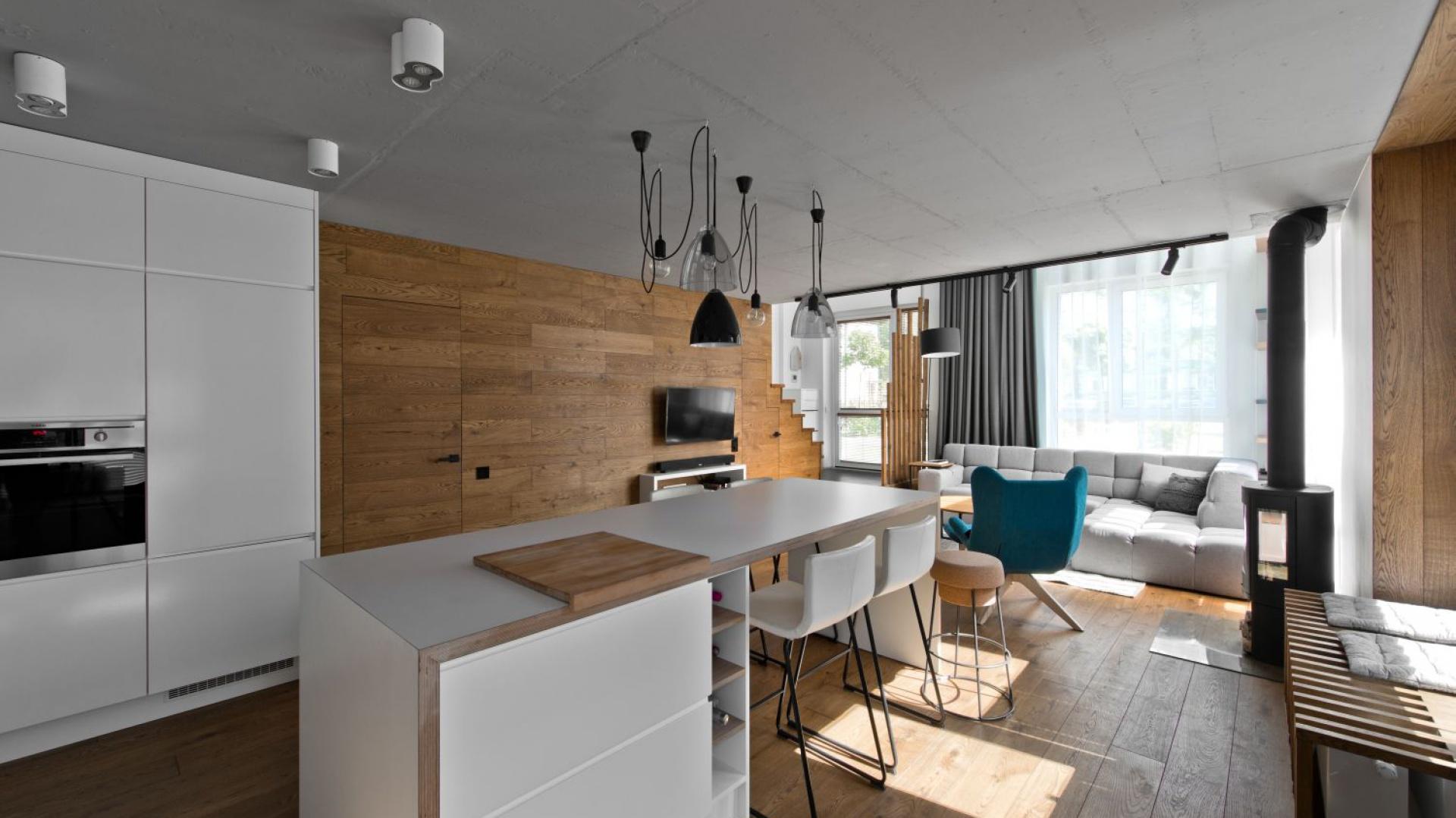 Z salonem sąsiaduje kuchnia wykończona w  bieli i drewnie. Projekt: arch. Indre Sunkodiene. Fot. Leonas Garbačauskas
