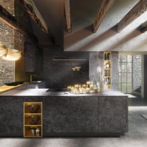 Surowe ceramiczne fronty zabudowy kuchennej przełamują polyskujące lampy nad barkiem w złotym kolorze. Fot. Alno AG, meble z programu Alnocera