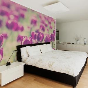 Kwitnąca łąka rozpościera się na całej ścianie za łóżkiem w sypialni Fot. Big-trix