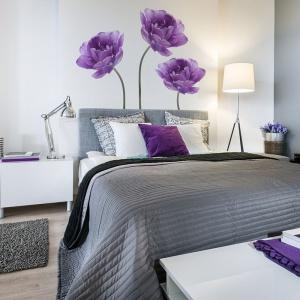 Ścianę nad łóżkiem udekorowano kolorowymi naklejkami przedstawiającymi fiołkowe kwiaty. Fot. Big-trix