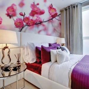 Ścianę nad łóżkiem zdobi kolorowa fototapeta ze zdjęciem pięknych kwiatów wiśni. Fot. Dekornik