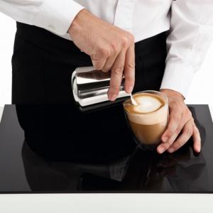 Serce - krok drugi.  Gdy  filiżanka jest już do połowy pełna, zbliż dzióbek do powierzchni kawy bez zmiany tempa nalewania mleka, tak by uzyskać biały okrągły kształt. Fot. Philips
